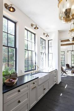 Long two tone galley style kitchen boasts a farmhouse sink is fitted with a polished nickel brass faucet positioned in front of a wall lined with black framed windows lit by brass swing arm sconces shining down over black quartz countertops placed atop white shaker cabinets finished with brass hardware as Urban Electric Co Urban Smokebell pendants hang above dark wood plank floors. #LampKitchen