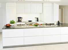 The brief was to provide a kitchen design ideal for family cooking, yet blend into the background when the dining and lounge areas were in use. The result is the kaolin laminate b1 kitchen seen here. The perfect geometry of the shapes, handle free units and flush hob all contribute to the unobtrusiveness of the kitchen. The extensive granite worktop adds some colour and texture whilst providing plenty of preparation surface. Kitchen by bulthaup Winchester.