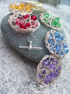Rainbow Crochet Wire Bracelet by SioniWinwns - This bracelet is made of beaded crochet wire circles. The circles have red, orange, yellow, green, blue and purple beads of different sizes. The wire is silver plated copper. When closed with it's silver plated toggle clasp, the bracelet is a loose fitting 21cm