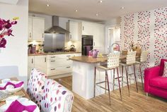 Interior Designed Kitchen, Dining, Family room, using Scion interior fabrics, raspberry, fuchsia, mauve and cream colour scheme with bamboo effect wood flooring - great use of a bar/island.  I just love that Scion wall paper.  David Wilson Homes 2015.