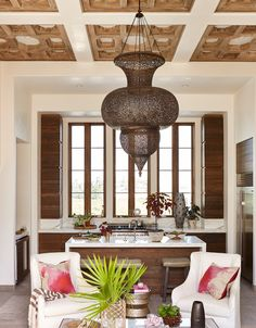 A 5-foot-tall brass lantern, custom-made in Morocco, anchors the combined kitchen-living area, where more than 1,000 sandblasted white oak pieces create a square pattern on the custom ceiling.