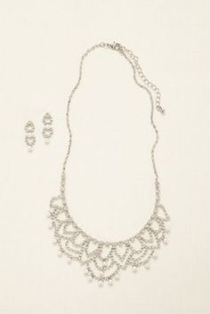 Add a touch of glam to your neckline with this sparkling scalloped necklace and earring set!  This scalloped necklace is adorned with crystals and peals with dainty drop earrings to match.  Available in Crystal/Silver.  Imported.