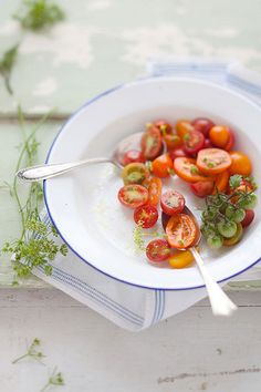 early summer  Love the contrasting red green and blue against the subtle back drop. Love how the bowl and the napkin work together, the dreamy lighting and the two spoons meant for sharing. The tiny green tomatoes are an unusual garnish