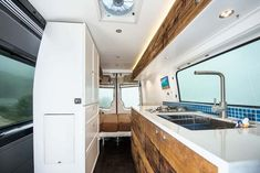 Interior of a built-out Sprinter van conversion. This camper van has beautiful white countertops and wood finish.