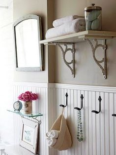 boost the storage options of a small guest bath with shelving and hooks attach bracketed shelves to walls to help keep the countertop