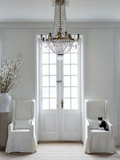 All White Foyer - pair of chairs flanks French doors