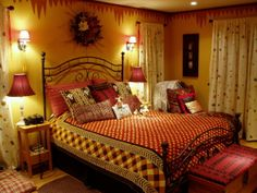 african influenced bedroom, A master bedroom with an african safari theme. A colorful bedspread covers a wrought iron bed. A freestanding mi...