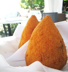 """""""Arancino siciliano"""" Arancino (Sicily). A street food of Sicily,  made with rice, a smidgen of ragù (meat sauce), peas and  cheese. The ingredients are rolled into a ball and fried until they're a golden orange colour – hence the name arancino or 'little orange'."""