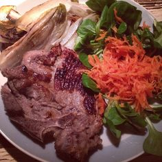 Schweinekotelett mit geschmortem Chicorée, Feldsalat und fermentierten Möhrenraspeln.   Pork chop with braised chicory, lamb's salad and homemade lacto-fermented shredded carrots.