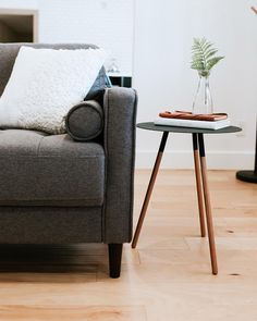 Modern gray mid century sofa, minimal round black and wood side table / end table, and beautiful light natural beech engineered hardwood floors. Modern interior design inspiration for the living room.