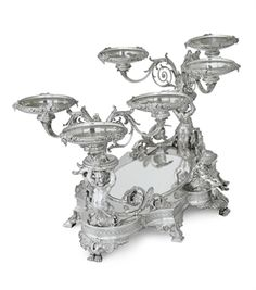 A RARE SILVER MIRROR PLATEAU CENTERPIECE  MARK OF TIFFANY & CO., NEW YORK, CIRCA 1870, DESIGN ATTRIBUTED TO JAMES H. WHITEHOUSE  Set on eight bird's-claw and acroteria feet, the base shaped astragal with ovolo and rosette medallion border, centering an oval mirror, two sides set with putti wielding sickles and wheat stalks, each end set with putti terms supporting three leaf-clad scrolling branches, each set with a removable circular dish...   48 in. long; 553 oz. gross weight