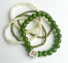 Set of 5 hand made bracelets made of sand beads and emerald green pearls with rose.