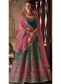 Teal and Pink Embroidered Velvet Lehenga features a beautiful velvet lehenga alongside a net pallu. Embroidery work is completed with zari, thread, and stone.