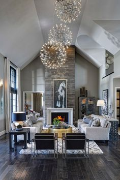 Living room, great room, dark rustic wood floors, stone fireplace, orb chandeliers, horse art | Moceri Homes
