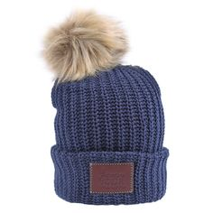 This pom beanie is knit out of 100% cotton yarn in a navy color. It features a brown leather patch that is debossed with the Love Your Melon logo and a detachable, natural faux fur pom. Made in the US