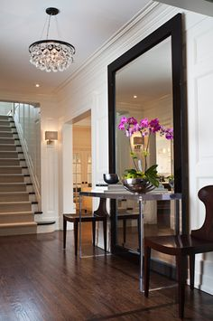 A mirror in the foyer expands the space & reflects the decor of the wall opposite.