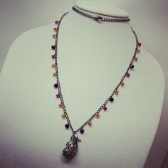 Gypsy Wine. A colorful piece to add to the fall wardrobe. An antiqued silver filigree wine pitcher on a long gunmetal chain, accented with purple, gold, orange, and fuschia crystals. #shopsmall #shoplocal #buyhandmade #supportsmallbusiness #handmadejewelry #baublesstudio #jewelry #wine