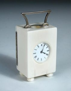 Sale F251115 Lot 701  A French ivory cased miniature carriage timepiece, with shaped silver handle and hinge to the rear door engraved to the inside 'June Corner', raised on four bun feet h:8 cm  - Cheffins