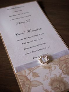 This wedding invitation called Champagne and Roses has been made using champagne pearlescent card (250 gsm), cream and champagne floral deco paper, white satin ribbon and a round crystal buckle. It comes with a white envelope. (https://www.etsy.com/listing/102359406/champagne-and-roses-wedding-invitation)