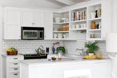 To avoid moving the plumbing, Kevin kept the kitchen's original footprint but updated the cabinetry, appliances, and fixtures. He replaced the dated cabinets with easy-to-access open shelving and Shaker-style lower cabinets. Instead of a bulky refrigerator, he installed a two-drawer version in the wet bar area, just across from the kitchen, placing prominence on cocktails rather than frozen treats.