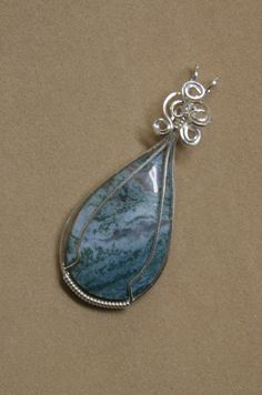 Teardrop shape moss agate cabachon--blue/green and white with transparent areas--wrapped in sterling silver. 1 and inches long Wire Pendant, Wire Wrapped Pendant, Wire Wrapped Jewelry, Wire Jewelry, Jewelry Crafts, Beaded Jewelry, Handmade Jewelry, Jewlery, Stone Wrapping