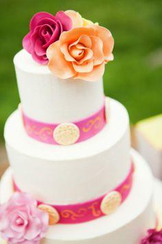 Pastel de boda blanco, decorado con cintilla rosa y flores comestibles