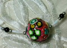 Poylmer clay beaded necklace has  flower shape patterns on it