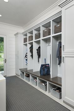 Long mudroom features closed cabinets flanking open mudroom lockers, one for each family member, lined with gray woven baskets over coat hook and galvanized metal baskets tucked under built in mudroom bench alongside a gray grid rug placed in front of gla Mudroom Cubbies, Mudroom Laundry Room, Mud Room Lockers, Mudroom Cabinets, Storage Cabinets, Mudrooms With Laundry, Entry Way Lockers, Built In Lockers, Home Lockers