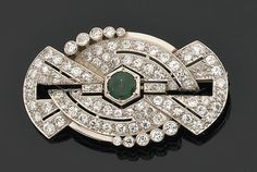 Broche ovale à décor de draperie stylisé. Au centre une émeraude ronde sur un pavage de diamants brillantés. Monture en or et platine. Années 1930.