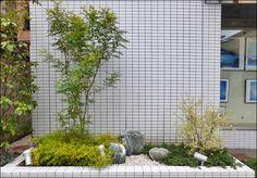 建設会社様のビル前に設置された花壇へ、コントラストの効いた洋風植栽をデザイン配置しております。イエローリーフとダークグリーンが交互に配置された植栽空間へ、庭石と砂利によるアクセントが加わっております。エントランス前にはプランター植栽も併せて設置をさせていただきました。
