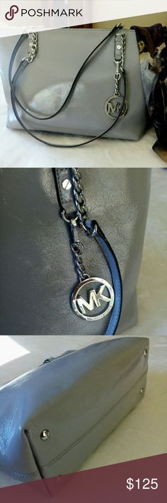 """🍸Michael Kors Jet Set Patent Leather EW Tote Used one time. Michael by Michael Kors! In beautiful shape. No issues. Authentic. Measurements are approximately 14"""" W x 9"""" H x 5"""" D. Silver chain handles are approximately 12"""" high. Well made zippers. Exterior slip pocket, four interior slip pockets with one zippered pocket. Hang tag is in great shape. Four silver tone feet for protection. Please use zoom feature for close ups. Michael Kors Bags Totes"""