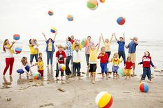 Extended family pictures on the beach with beach balls. Clothing color ideas.