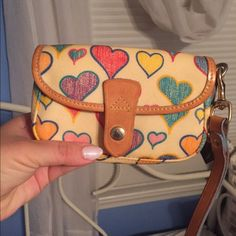 Dooney and Bourke heart wristlet Db heart wristlet. Used but well taken care of. Shows some darkening  around the edges of the tan leather. Little yellowing on the top flap on the white part Dooney & Bourke Bags Clutches & Wristlets
