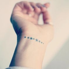 Pequeño tatuaje de ocho estrellas en la muñeca.