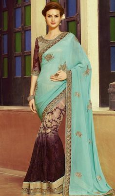 Women attractiveness is magnified tenfold in this navy blue, wine and beige color shade georgette net embroidered sari. The stones, lace and resham work looks chic and fantastic for any function. Upon request we can make round front/back neck and short 6 inches sleeves regular saree blouse also. #latestdesignersaree #eveningwearsarees #stylishsari
