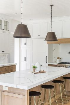 Gold and black backless stools sit at a caramel stained island topped with statuary quartz countertops lit by two dark nickel lights hung from a white shiplap ceiling.