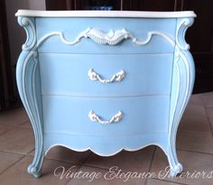 Beautiful night stand with ornate carvings and gorgeous curves, painted in a custom mix of Annie Sloan Florence, Greek Blue, and Pure White. Top painted in Old White. Baroque Art gilders paste in cream used on carvings.  By Vintage Elegance Interiors.