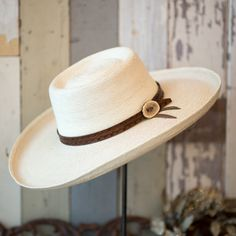 "$100.00   ""Patrician"" light palm hat with leather hat band.  -4"" brim.  -Hand tooled hat band with antler button (All bands are unique and will not be exactly as pictured)  -Hat band comes in four different colors: Black, Dark Brown, Brown, & Saddle Tan.   *When ordering online please write your hat size in the notes, or call the shop at 214-821-1777  **This hat is a custom order please allow an extra week for processing."