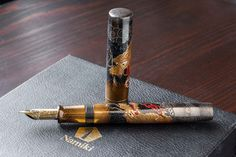 This Namiki Emperor fountain pen was just released in late 2016 and has been decorated with Maki-e by the skilled artisan Mamoru in Japan. It features the Togidashi-Taka Maki-e technique (burnished-raised maki-e), and depicts two dragons, one on the cap and one on the barrel. Raden abalone shells accent the background. The pen has a medium 18kt gold nib, fills via eyedropper, and comes packaged in a wooden box with a bottle of ink. <br><br><i>Please allow us up to several e...
