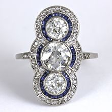 Vintage Art Deco Three-Stone Diamond & Sapphire Ring: Circa 1920's. Straight out of the Prohibition era of the 20's, this stunning art deco three stone ring is the statement piece you have been looking for. Set with diamonds and a sapphire halo in platinum.