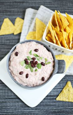 Creamy black bean dip. 15 ounces (one can) black beans, rinsed and drained Two 8-ounce packages cream cheese* 3 cloves garlic 1 small onion (or half a medium-sized one) 2-3 tablespoons chopped cilantro 8 ounces cherry tomatoes (or any tomatoes you have/like) 1/4 teaspoon cayenne powder (or more if you like it spicy) 1 lime salt and pepper to taste