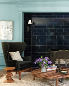 """In the living room, Bestor ripped out the traditional wood paneling and lined the fireplace with a glossy blue tile. The expanse of tile looks modern and adds texture, and in combination with the teal walls, it """"creates a kind of nice underwater experience"""" in the low-light room, says Bestor. A word to the wise: When using a strong paint color like this, you want the walls to be perfectly smooth, without visible bumps or ridges. (So hire someone if you're not sure you're up to the task.)…"""