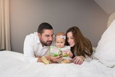 Parents reading to their 1-year old baby girl on the bed. Lifestyle family photo by N. Lalor Photography.