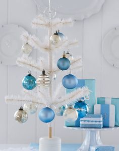 White as a Feather --This whimsical white feather tree is a nod to the early 20th century. With a crisp white frame that contrasts boldly with rich blue and metallic ornaments, this tree is a fresh and modern twist on traditional holiday décor. These festive trees look great on hallway tables, end tables, or even placed on the floor in the corner of a room.
