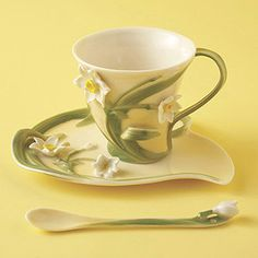 Two's Company Narcissus Tea Set: Two's Company Narcissus Tea Set.  A shapely flower petal saucer and delicate cup in hand painted porcelain inspired by its real life counterpart. Soft yellow background with moss green accents. Three piece set includes teacup, saucer and spoon.  5 1/2
