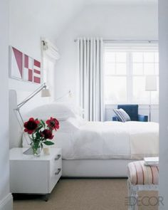 Coastal Living ~ In Bobbie and Lew Frankfort's beach house in the Hamptons, interior designer Delphine Krakoff adds nautical touches to a bedroom, including framed flags made of red and white Coach leather, crisp navy and white cotton curtains and upholstery, and tailored stripes. The bedside table is from Cappellini Modern Age, and the table lamps are by Philippe Starck for Flos.