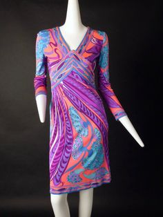 Awesome 1960s printed silk knit dress in a fluorescent coral, blue, turquoise, purple and white. The dress has a v0neckline with a waist yoke that comes to a point at the base of the neckline. Dart fi