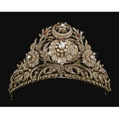A RARE OTTOMAN DIAMOND AND RUBY SET GOLD TIARA, TURKEY, CIRCA 1800.  The foliate openwork frame supporting attached elements set with cut-diamonds, the centre with a large diamond floral rosette radiating diamond-set petals issuing floral sprays set with diamonds and rubies, the crown with a star and crescent motif, suspension loops to the sides. (Via Sotheby's)