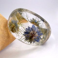 Just when I think these can't get any more pretty - I see this one.  A resin bracelet with Nigella flowers inside.  Really - how could you not have a good day with this on your arm?
