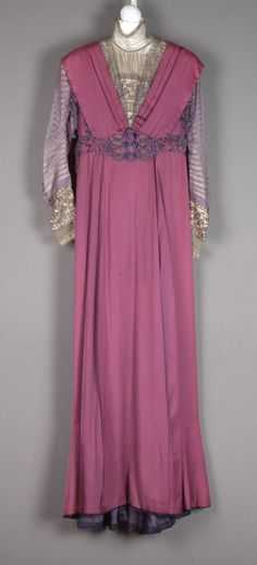 Dress Designer: Mme.J. Baer Date: ca. 1908–1910 Media: Silk Satin, Silk Chiffon, Silk Cord, Metal Thread And Silk Embroidery Country: United States Accession Number: 55015.2 Dress of purple satin, purple chiffon, and metallic lace; high neck collar and inset of metallic lace over cream silk at center front and back; purple satin bodice pleated over shoulders into point at center front and back waistband; long chiffon sleeves with horizontal tucks; deep cuffs of metallic lace.